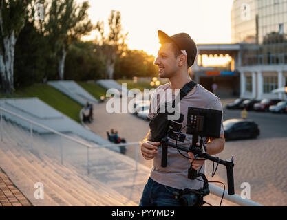 Videographer with video equipment, steadicam 3 axis gimbal - Stock Photo