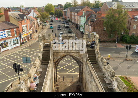 Sunny high view of people sitting at cafe tables on top of historic Walmgate Bar, road junction, traffic & shops - York, North Yorkshire, England, UK. - Stock Photo