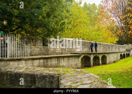 Autumn day & man & woman stand together looking out from walkway on beautiful scenic historic medieval York city walls - North Yorkshire, England, UK