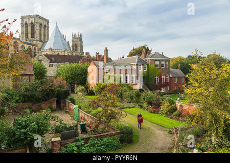 Scenic view of historic buildings from city walls - Grays Court (gardener working) Minster & Treasurer's House - York, North Yorkshire, England, UK.