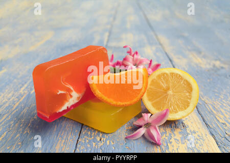 Handmade natural soap with and natural ingredients: lemons and oranges, on rustic wooden board. Spa concept - Stock Photo