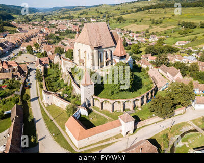 Biertan town and fortified church in Transylvania, Romania. Medieval castle on a hill, high spires, walls, red tiled roofs, surrounded by a village. - Stock Photo