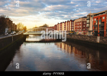 Embankment of Liffey River in Dublin, Ireland. Sunset view with buildings and city lights at the background - Stock Photo