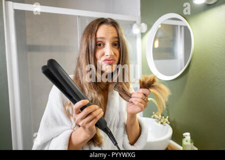 Portrait of unhappy woman holding splitting hair ends and hair straightener in the bathroom - Stock Photo