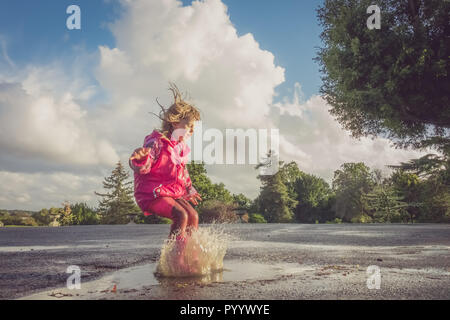 Little Caucasian girl jumping into the puddle after rain in english countryside - Stock Photo