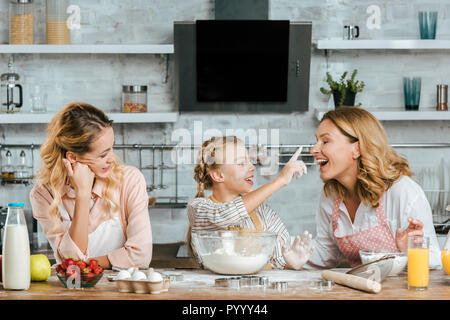smiling little child preparing dough and playing with mother and grandmother at home - Stock Photo