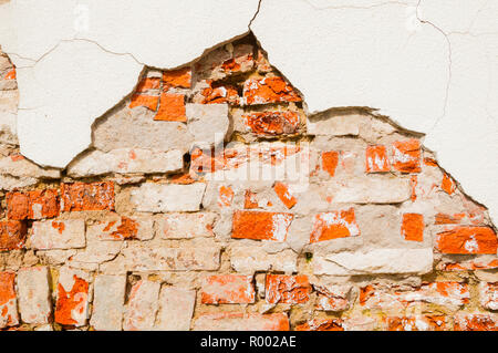 Stone texture background of weathered red brick stone wall, texture of stone red bricks with flaked stucco - Stock Photo