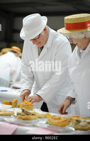 A pair of judges examine pies and other meat produce at a regional competition for producers.