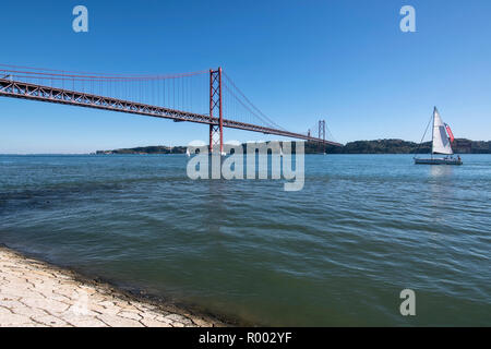 Sailboat on the Tagus River (Rio Tejo) with Ponte 25 de Abril suspension bridge and the statue of Christ, Cristo Rei, Lisbon, Portugal. - Stock Photo