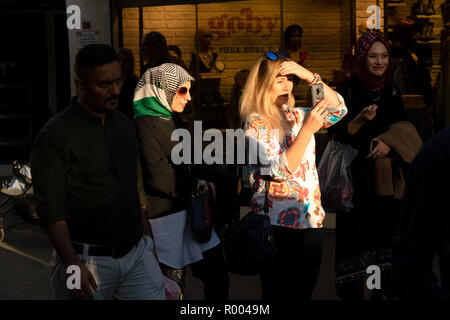 Istanbul, Turkey - October 29, 2018 : Turkish young women are at street in front of a store. One of them is taking photo with her phone. - Stock Photo