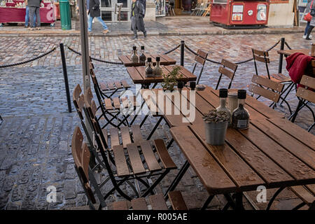 Wet Sunday morning, Covent Garden Market, London. Outdoor restaurant tables after rain - Stock Photo