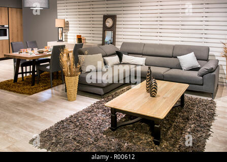 Spacious open plan kitchen, dining room and living room interior with grey upholstered lounge suite, rug, set table and wooden floor in a modern house - Stock Photo