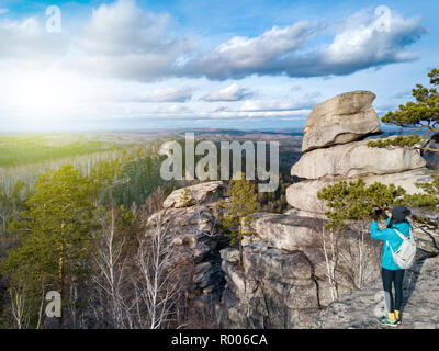Drone view of brave girl making a panoramic photo of spectacular landscape on the cliff edge; successful ascent of mountain, tranquility and serenity  - Stock Photo