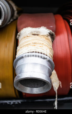 a coiled fire hose with steel nozzle - Stock Photo