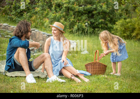 happy Family picnicking outdoors with their cute daughter, blue clothes, woman in hat - Stock Photo