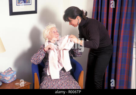 carer helping old lady to dress - Stock Photo