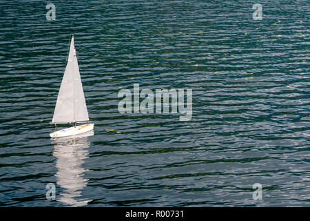 White sailing yacht model floating in the lake. - Stock Photo