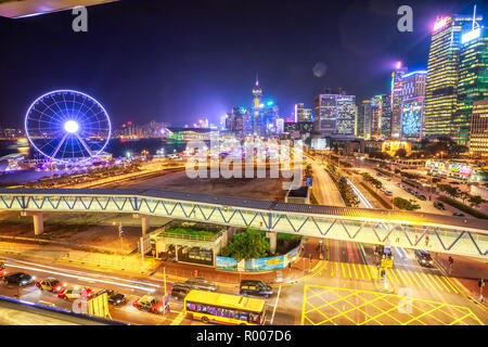 Hong Kong, China - Jannuary 23, 2017: Scenic aerial view of cityscape in Hong Kong, Central District, with Observation Ferris Wheel at Victoria Harbour illuminated at night. Urban night city for asian traveler destination. - Stock Photo