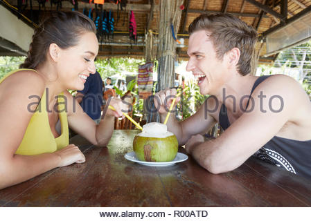 Young couple drinking from coconut with straws - Stock Photo