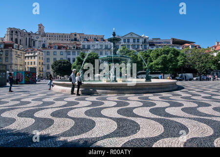 Rossio Square in the city center, Praca de Dom Pedro IV, with fountain in the Baixa district, Lisbon, Portugal. - Stock Photo