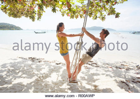 Young couple on beach swing - Stock Photo