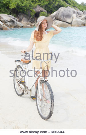 Young woman wearing yellow dress with bicycle on beach - Stock Photo