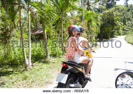 Young man and woman riding moped - Stock Photo