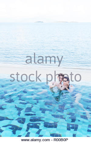 Young couple taking selfie in swimming pool - Stock Photo