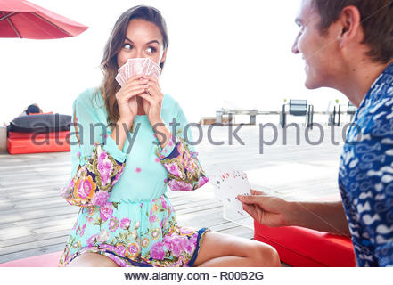 Young couple playing cards on deck - Stock Photo