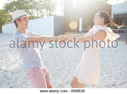 Young couple holding hands while spinning on beach