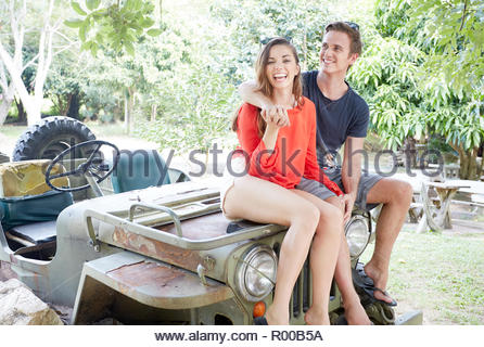 Young couple sitting on back of tractor - Stock Photo