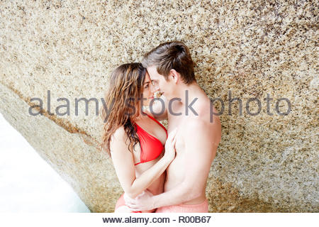 Young couple embracing by boulder on beach - Stock Photo