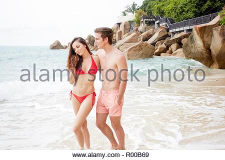 Young couple wearing swimwear walking on beach - Stock Photo