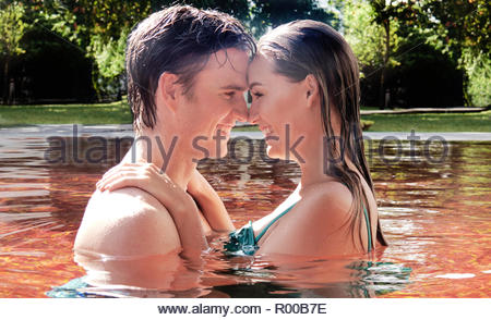 Young couple embracing in orange swimming pool - Stock Photo