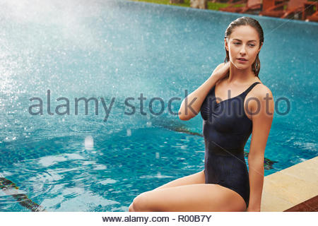 Young woman sitting by swimming pool - Stock Photo