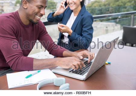Smiling young man using laptop on balcony - Stock Photo