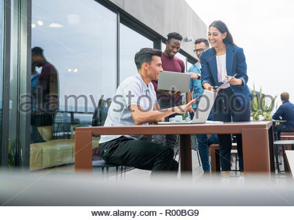 Colleagues using laptops on balcony - Stock Photo
