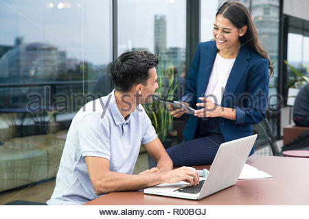 Colleagues using laptop and digital tablet on balcony - Stock Photo