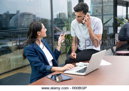 Colleagues using laptop and smart phone on balcony - Stock Photo