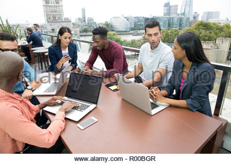 Businesspeople with laptops during meeting on balcony - Stock Photo