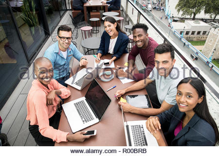 Smiling businesspeople with laptops during meeting on balcony - Stock Photo