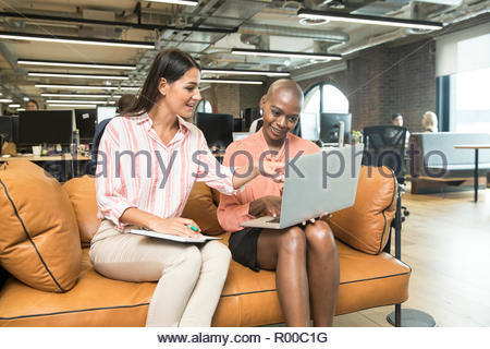 Businesswomen using laptop on sofa - Stock Photo