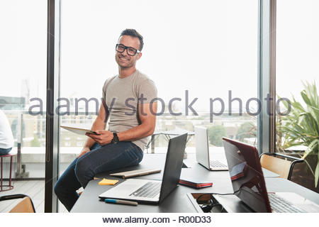 Young businessman holding digital tablet in conference room - Stock Photo