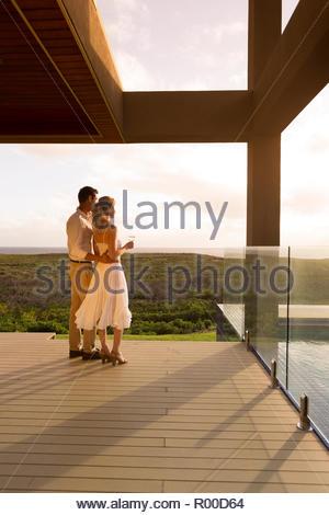 Couple holding white wine on balcony - Stock Photo