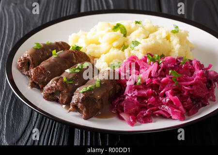 Beef rolls with mustard, bacon and pickles on a plate served with mashed potatoes and red cabbage close-up. horizontal - Stock Photo