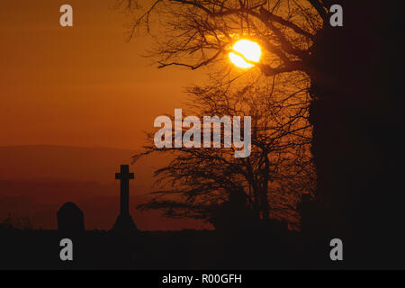 teh sun setting on lanssown cemetary in Bath with the cross and tree silhoutted - Stock Photo