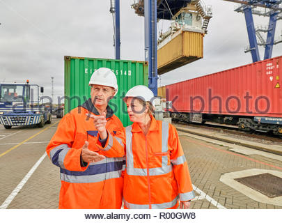 Dock workers talking by railway tracks at Port of Felixstowe, England - Stock Photo