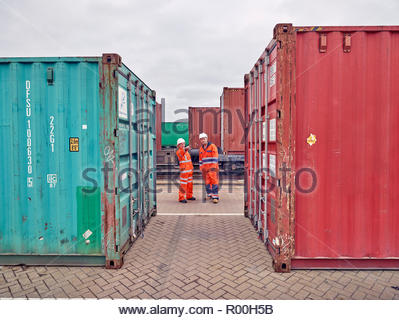 Dock workers between cargo containers at Port of Felixstowe, England - Stock Photo