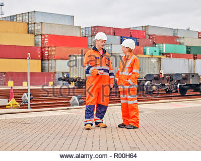 Dock workers talking by railroad tracks - Stock Photo