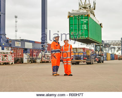 Dock workers by crane lowering cargo container onto truck - Stock Photo